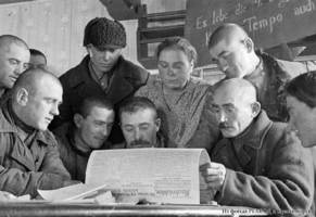 "Members of the ""Rot Front"" collective farm read about a government decree on purchase in the Nachrichten newspaper [which was the main newspaper of the Volga German region in German language], 1932."