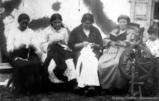 German village/colony residents at leisure - sitting on a bench mending clothes, a woman reading a book, a girl behind a spinning wheel. Approx. 1927-1928.